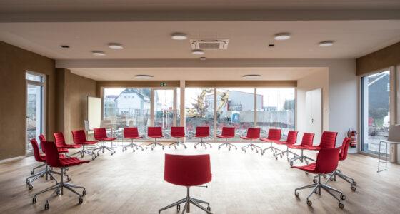 Innenansicht Seminarraum Momentum mit roten Stühlen